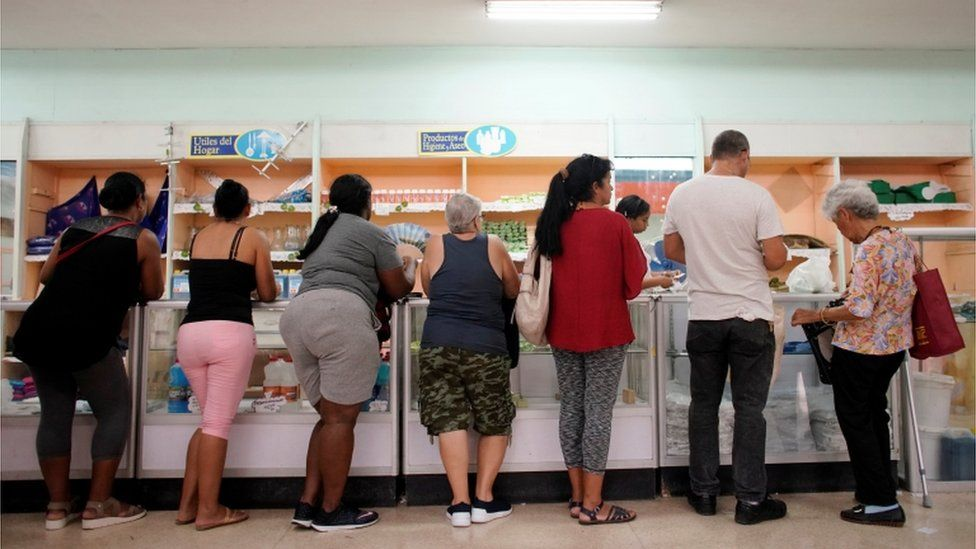 Cubans queue for products in a state shop in Havana