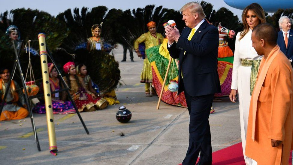 US President Donald Trump and First Lady Melania Trump are greeted by performers wearing traditional costumes as they arrive at Agra Air Base in Agra on February 24, 2020.