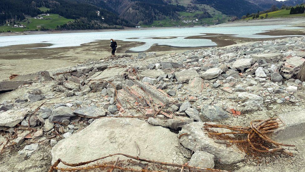 A person stands in the rubble at Lake Resia
