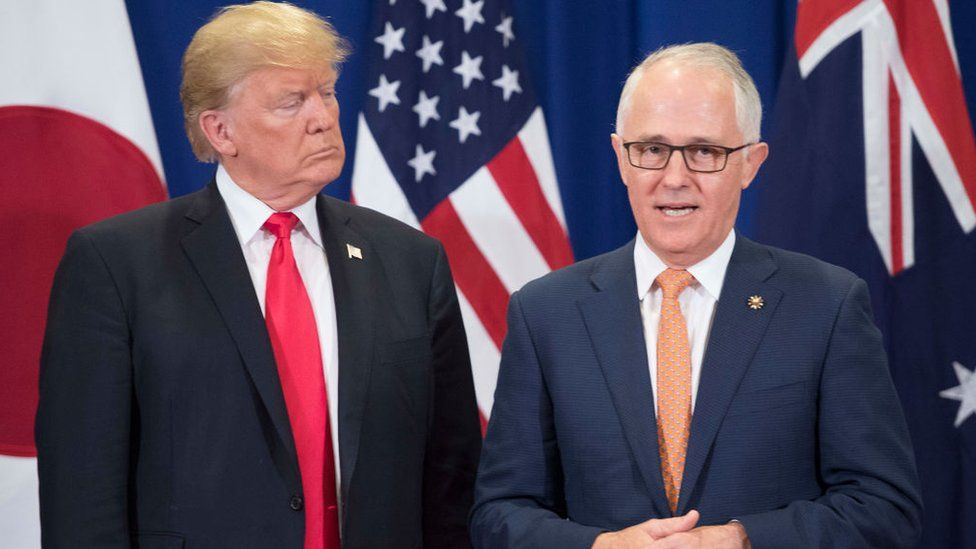 Donald Trump and Malcolm Turnbull stand in front their nations' flags during a meeting in 2017