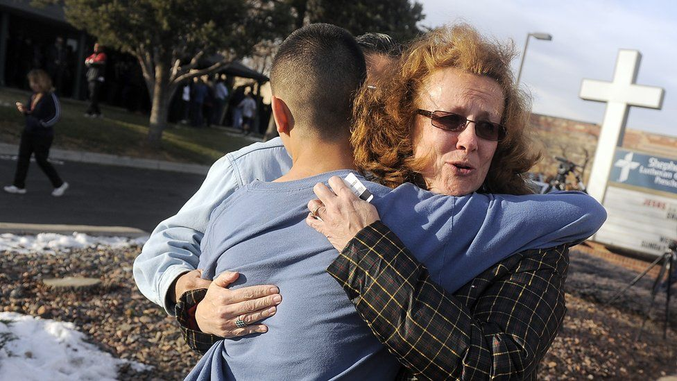 A parent embraces her child after a shooting at Arapahoe High School, Colorado