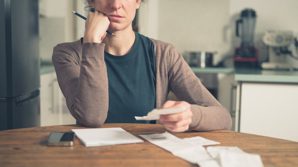 Woman studying bills and receipts