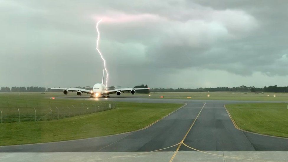 Lightning bolt behind the Emirates A380 plane at Christchurch Airport