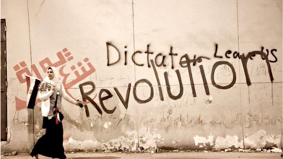 A woman walks past graffiti on a wall in Cairo (Feb 2011)