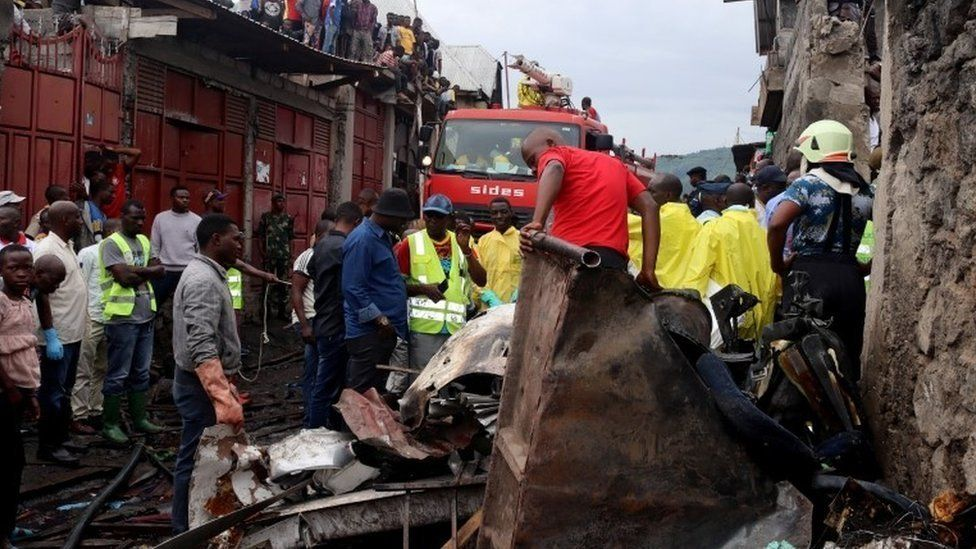 Rescuers and civilians gather at the site where a Dornier 228-200 plane operated by local company Busy Bee crashed into a densely populated neighborhood in Goma, eastern Democratic Republic of Congo November 24, 2019.