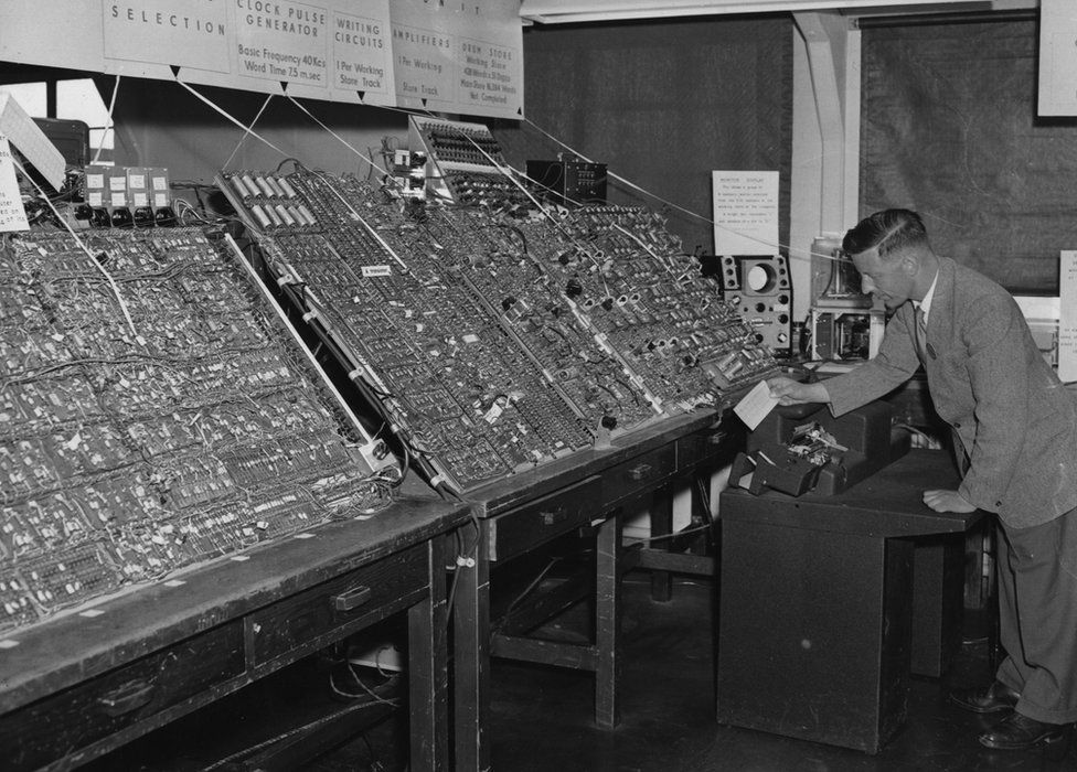 Man using a massive computer in 1956