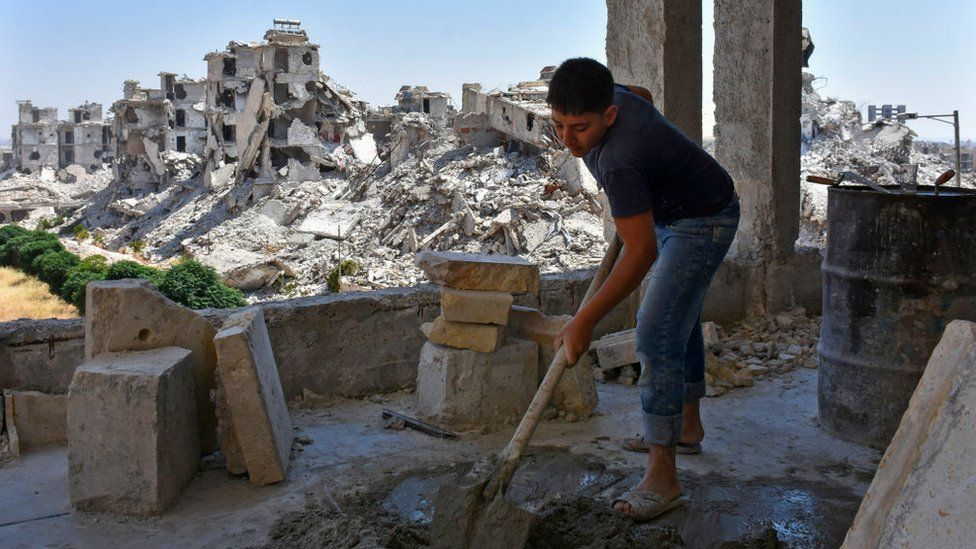 A Syrian labourer works as homes are rebuilt in Zahraa area of Aleppo (6 July 2020)