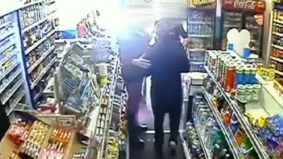 Mr Briggs walking out of shop with police officers before being restrained