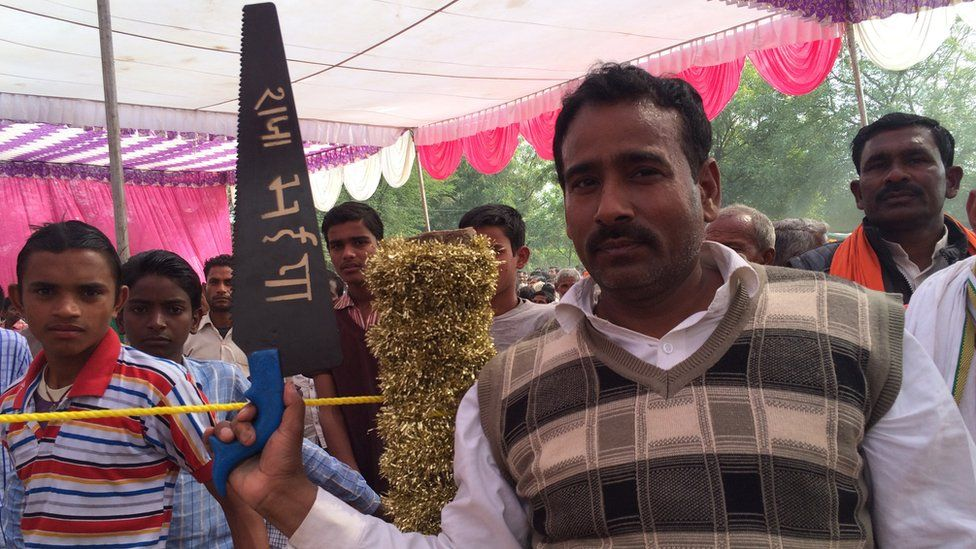 A Raja Bhaiya supporter with a wooden saw, his election symbol