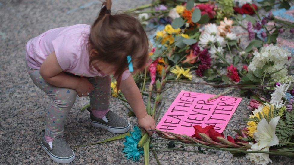 A young girl puts flowers on a memorial to Heather Heyer with a sign 'Heather Heyer matters'