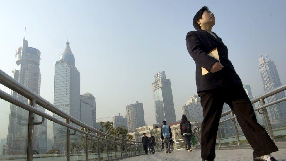 woman in suit walking across bridge