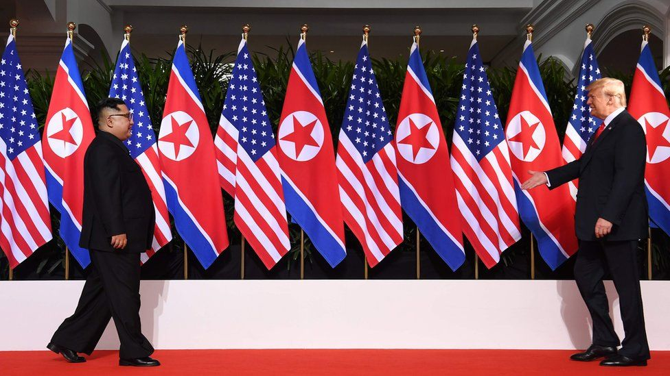 US President Donald Trump (R) and North Korea's leader Kim Jong Un (L) walk toward one another at the start of their historic US-North Korea summit, at the Capella Hotel on Sentosa island in Singapore on 12 June 2018.