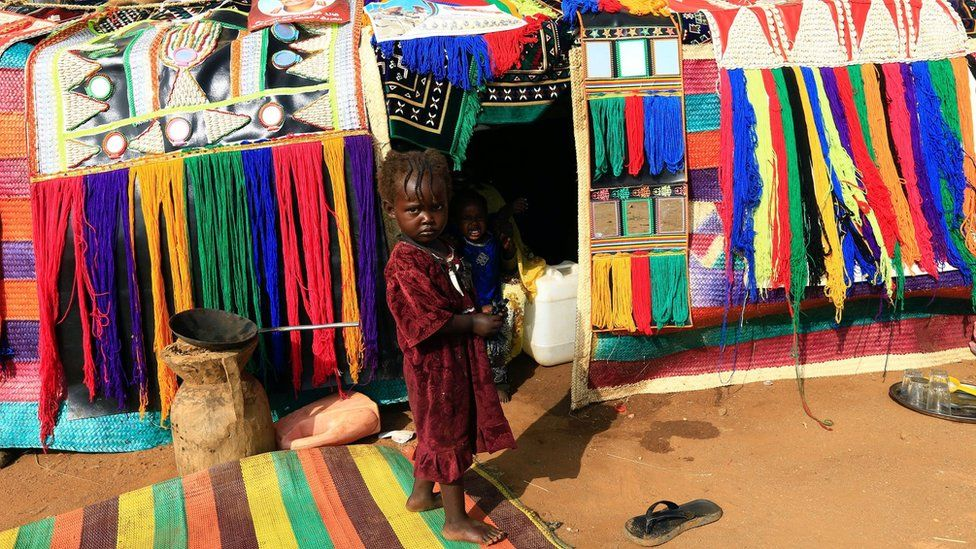 A child stands in front of a decorated house during the Sudanese president's visit to the war-torn Darfur region at Rapid Support Forces Headquarter in Umm Al-Qura, Darfur, Sudan (September 23, 2017)