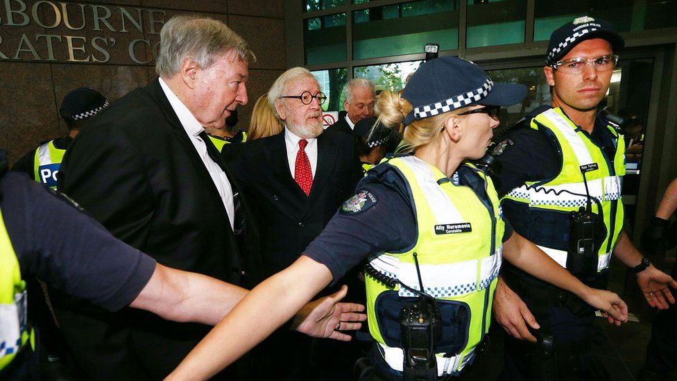 Cardinal George Pell and his lawyer Robert Richter are shielded by police upon entering court