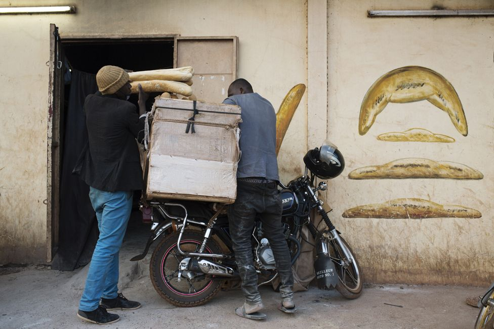 Alhassan Djitteye, who has been delivering bread for ten years, loads up his motorbike before heading out to make deliveries.