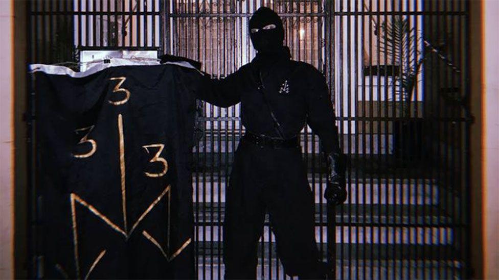 Masked man posing with ONA symbols