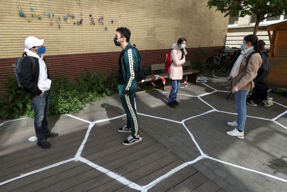 Students stand separately in designated hexagon shapes on the floor