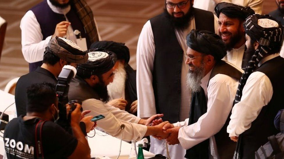 Taliban delegates shake hands during talks between the Afghan government and the Taliban in Doha, Qatar (12 September 2020)