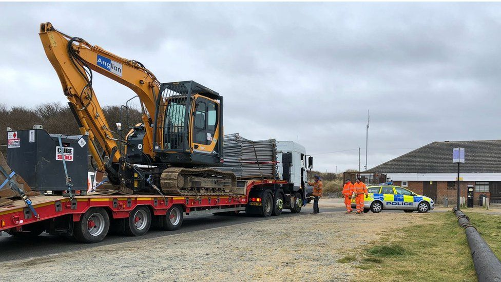 Digger on flat bed lorry
