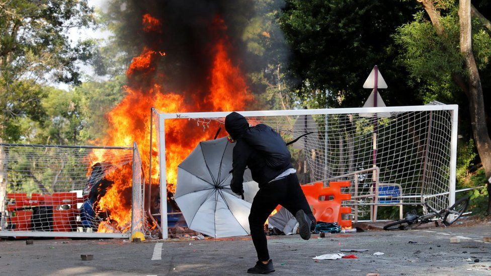 A university students throws an object at riot police