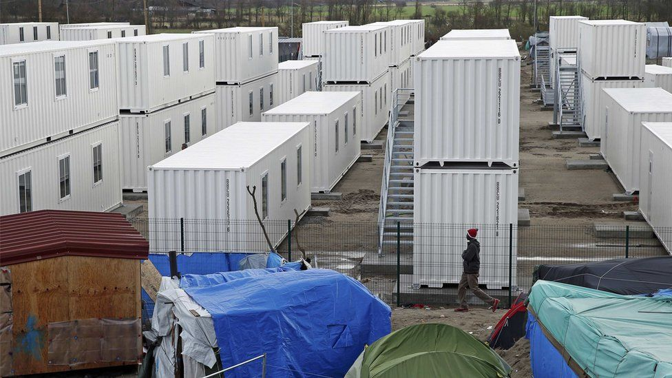 Containers are put into place to house several hundred migrants