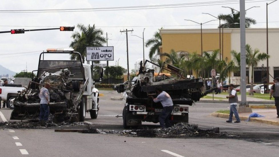 Officials remove burned vehicles away from a crime scene after an ambush perpetrated by alleged members of an organised crime syndicate in Culiacan, Sinaloa, Mexico (30 September 2016)