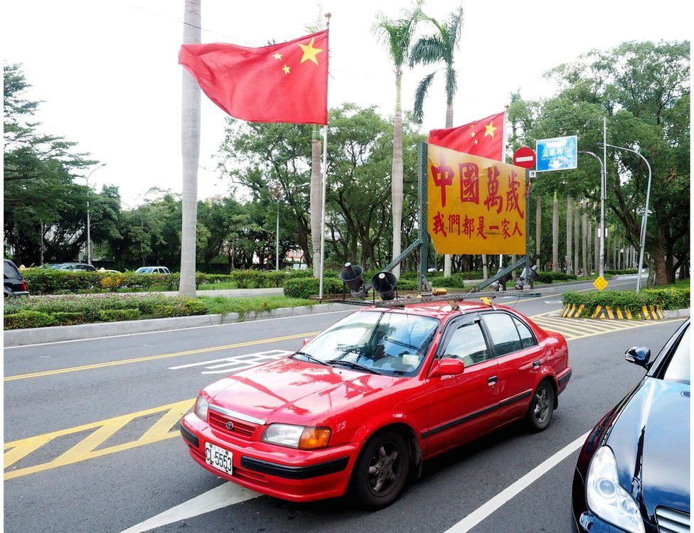 """A member of a pro-unification group drives a red car displaying China's national flags and a sign saying """"Long Live China. We Are One Family"""", to show support for the up-coming meeting between Taiwan""""s President Ma Ying-jeou and Chinese President Xi Jinping, in Taipei, Taiwan, 4 November 2015"""