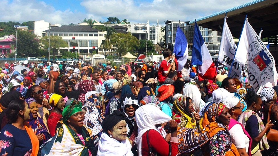 Protesters hold French and Mayotte flags as they gather on the Place de la Republique in Mamoudzou, Mayotte, on 13 March 2018
