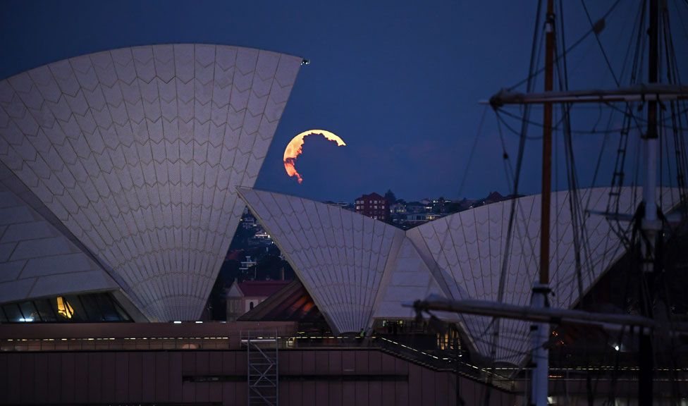 A pink supermoon obscured by clouds seen alongside the Sydney Opera House in Australia