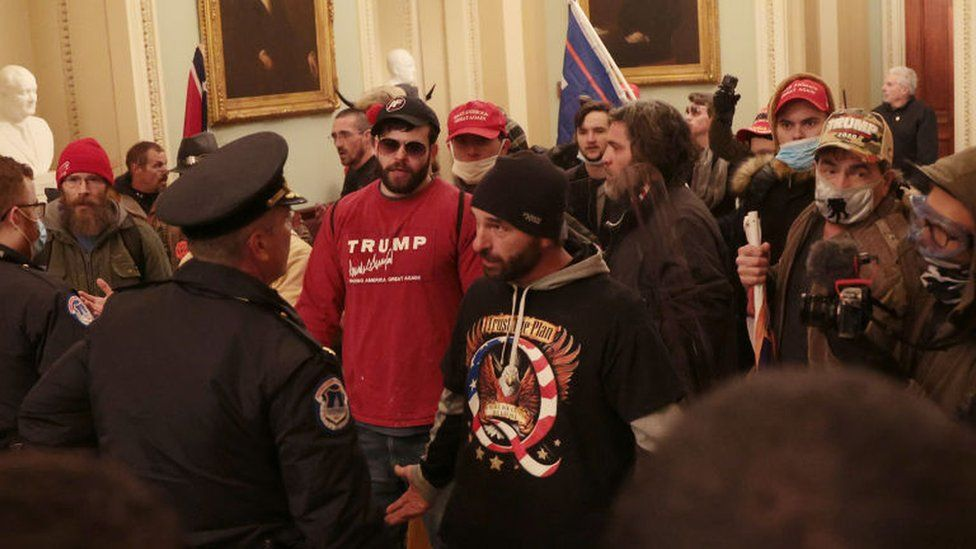 A protester wearing a Q shirt talks to police inside the US Capitol building on Wednesday