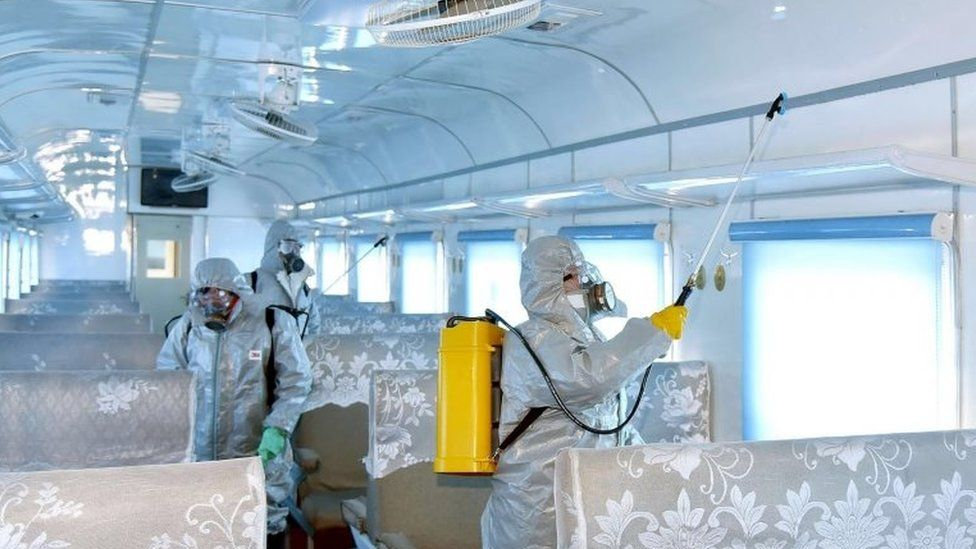 People in protective suits spraying disinfectant at an undisclosed location in North Korea