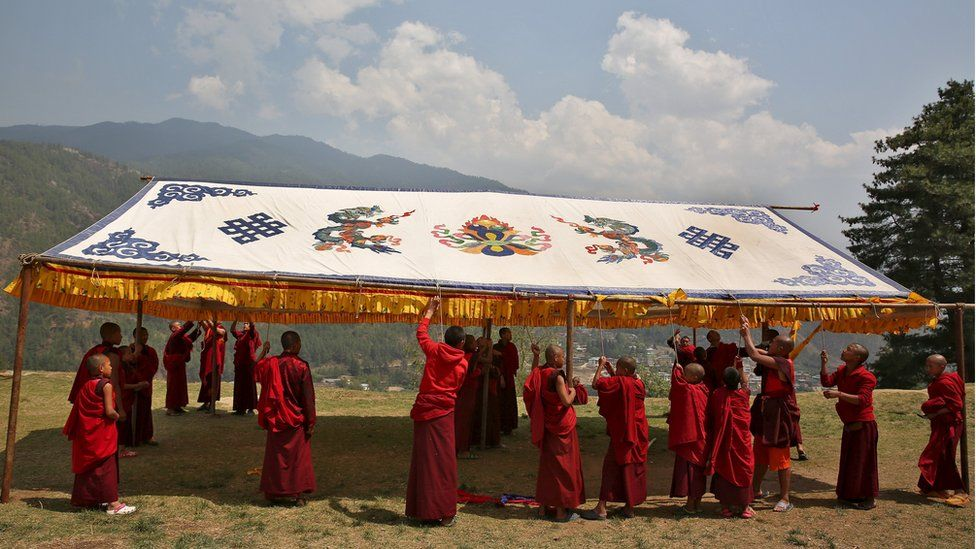 Monks put up a marquee in preparation for the UK royals' visit