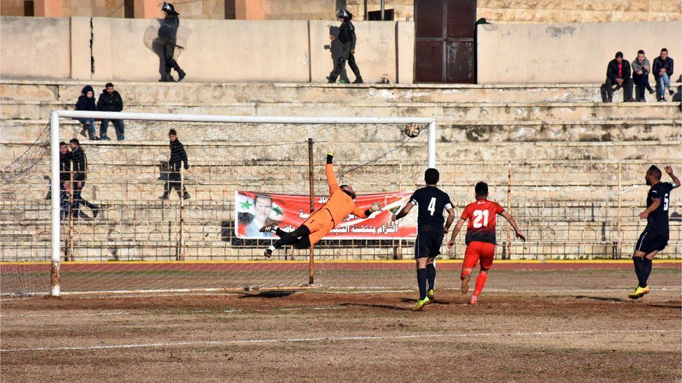 Al-Ittihad's goalkeeper dives towards the corner of his goal as a shot - apparently on target - soars towards goal