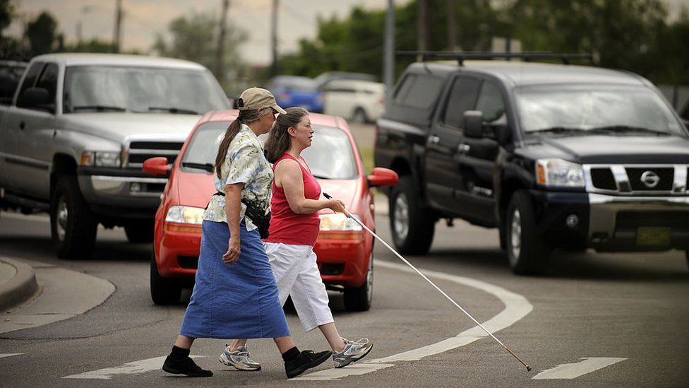 Janet Barlow offers guidance to Shelley Bruns crossing the street in Denver