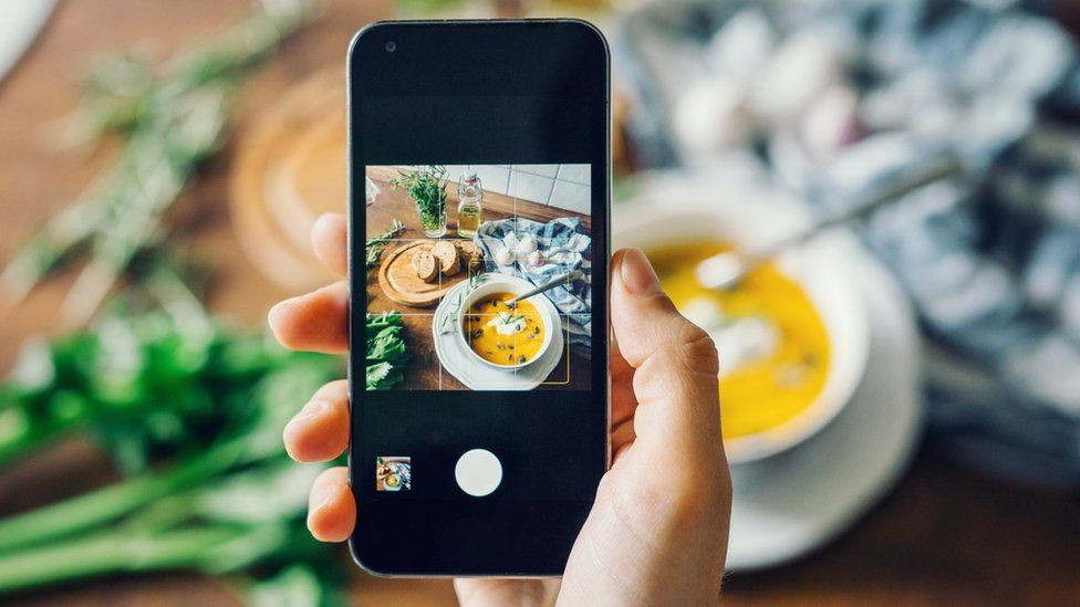 Hand holding a smartphone taking a picture on Instagram of soup
