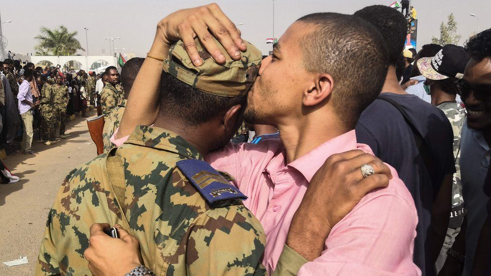 """A Sudanese anti-regime protester kisses a soldier on the head during protests on April 11, 2019 in the area around the army headquarters in Sudan""""s capital Khartoum"""