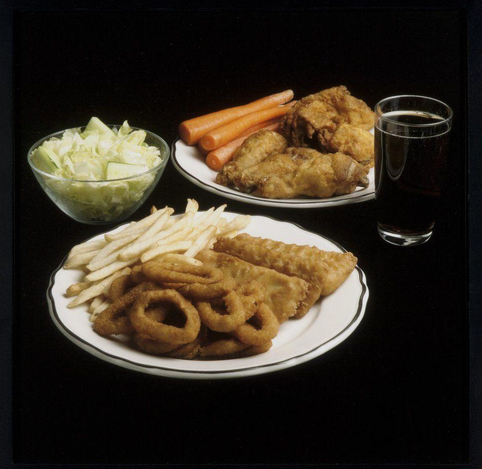 Lechuga, aros de cebolla, papas fritas, zanahorias y pollo frito.