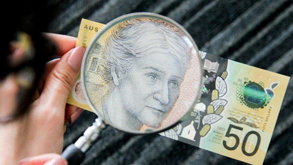 50 dollar note with magnifying glass