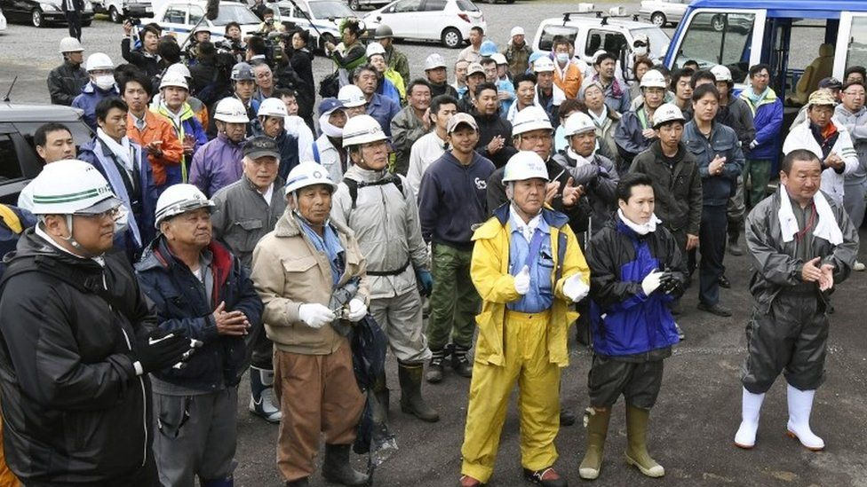 """Rescuers celebrate after a news that a missing boy was found, in Nanae town, on Hokkaido, the northernmost of Japan""""s four main islands Friday, June 3, 2016."""