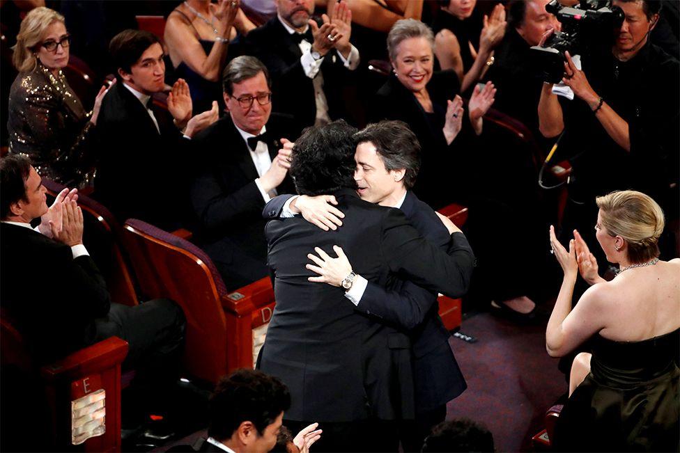 Director Bong Joon-ho receives a hug from Noah Baumbach