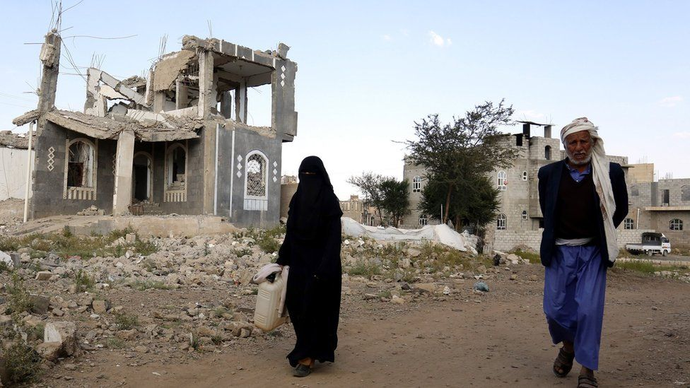 "Yemenis walk past a destroyed building allegedly targeted by a previous Saudi-led airstrike, in Sana""a, Yemen, 08 December 2018."