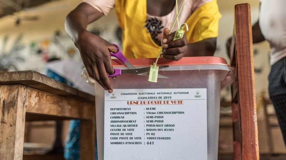 A polling official cuts the seal of a ballot box at a polling station during the elections for a new parliament in Cotonou on 28 April 2019.