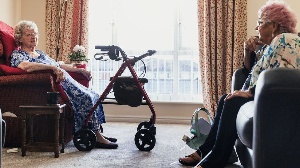 Two women chatting in a care home