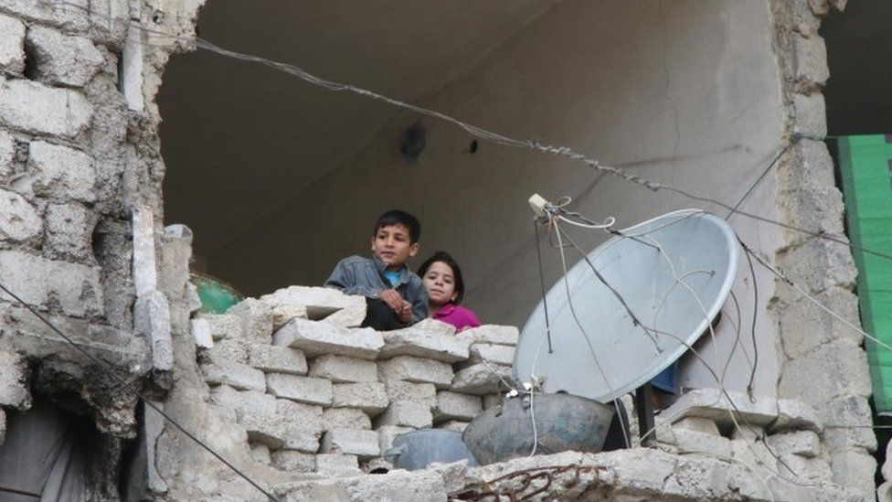 Children in partly destroyed building in Aleppo