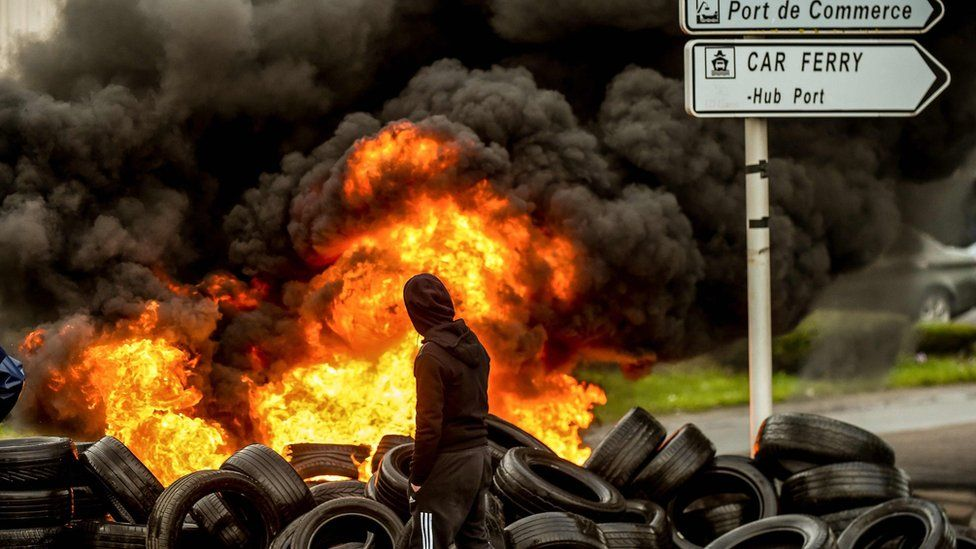 A fishermen from the French city of Boulogne walks past burning tyres blocking access to the port of Boulogne-sur-Mer on January 25, 2018,