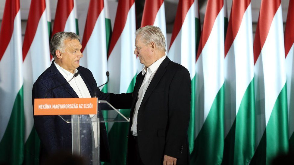 The two politicians stand at a podium with Hungary flags in the background