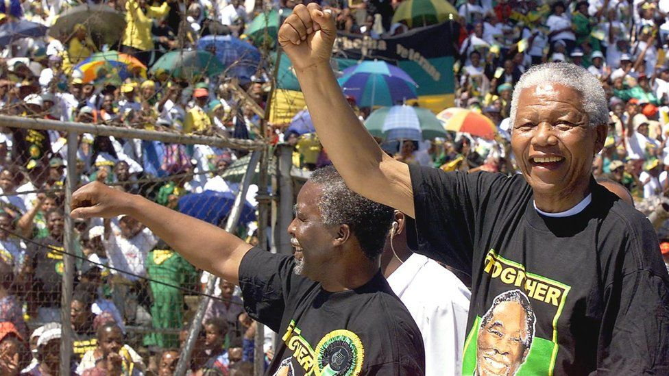 South African President Nelson Mandela (R) and deputy President Thabo Mbeki (L) greets the crowd from a pick-up truck during an African National Congress rally at the Orlando stadium in Soweto, 28 March 1999.