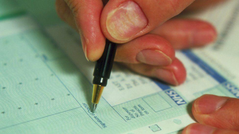 A close-up shot of a doctor writing a prescription