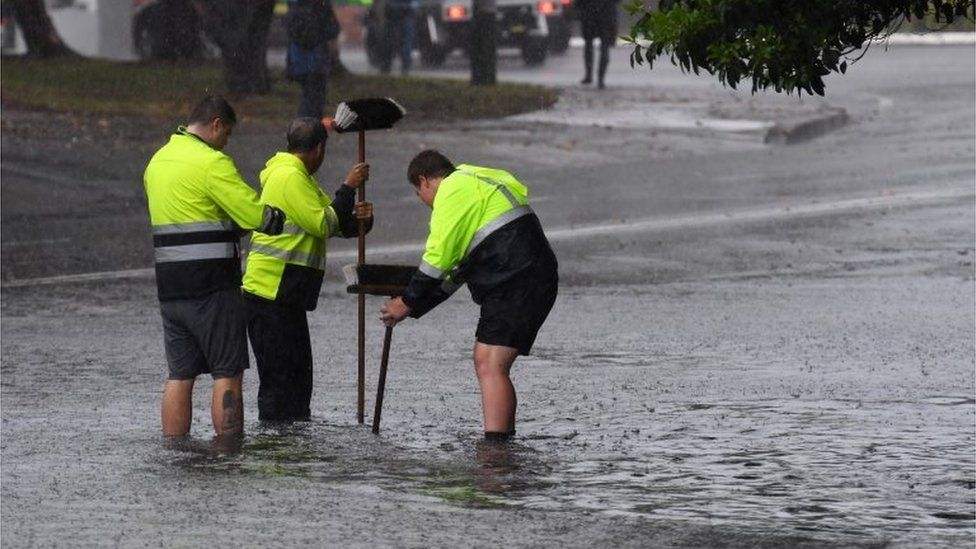Council workers standing in ankle-deep water attempt to clear a drain