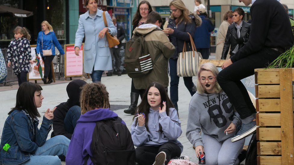 Young people sit in the street chatting